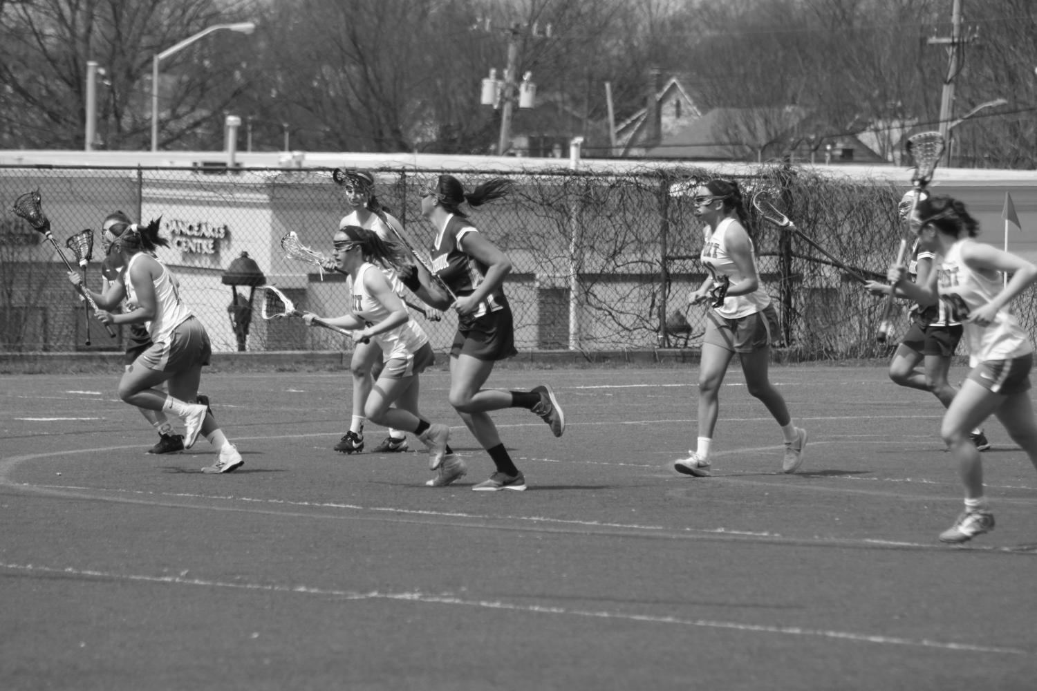 The+Vikings+girls+lacrosse+team+skirmishes+midfield+at+a+home+game+against+Lynbrook+on+April+10.+The+Vikings+won+the+game+15-7.