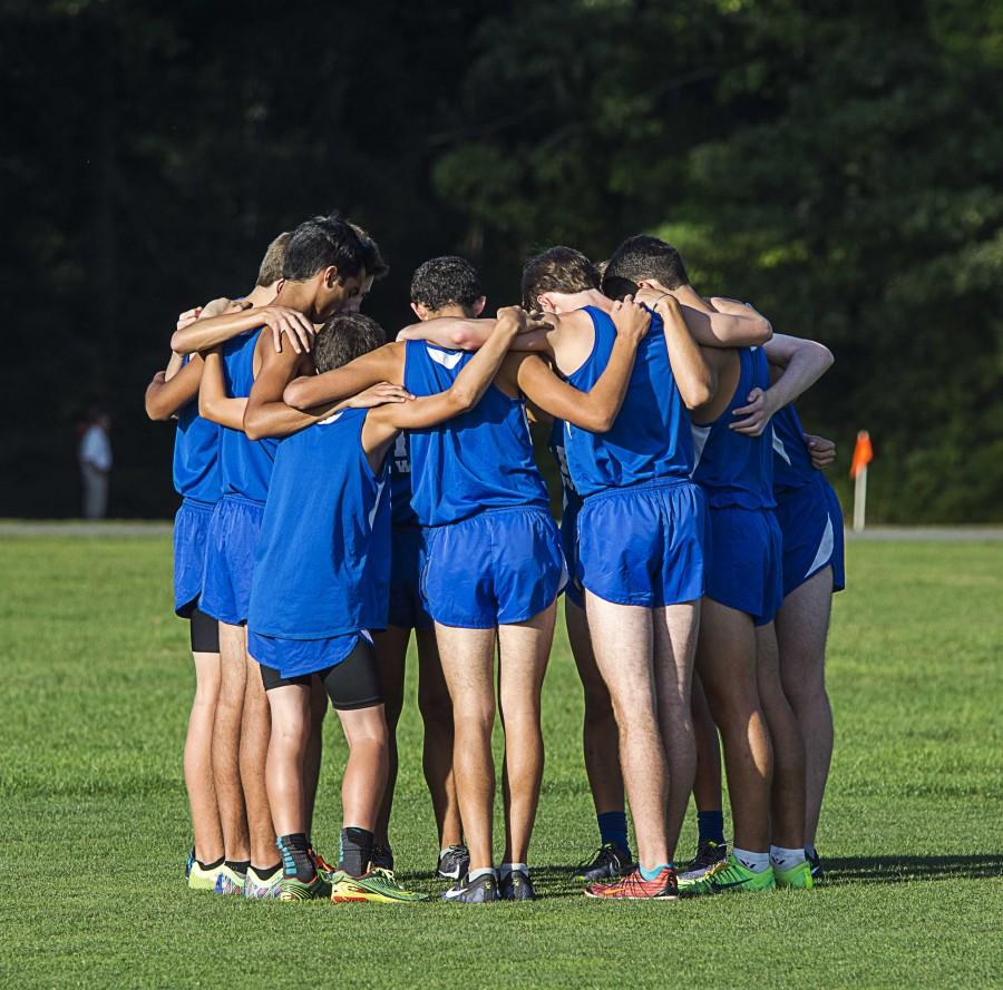 """The """"Varsity 10"""" huddles up before their 4k run on Sept. 24 at Bethpage State Park. The Vikings won the meet and remain undefeated so far this season."""