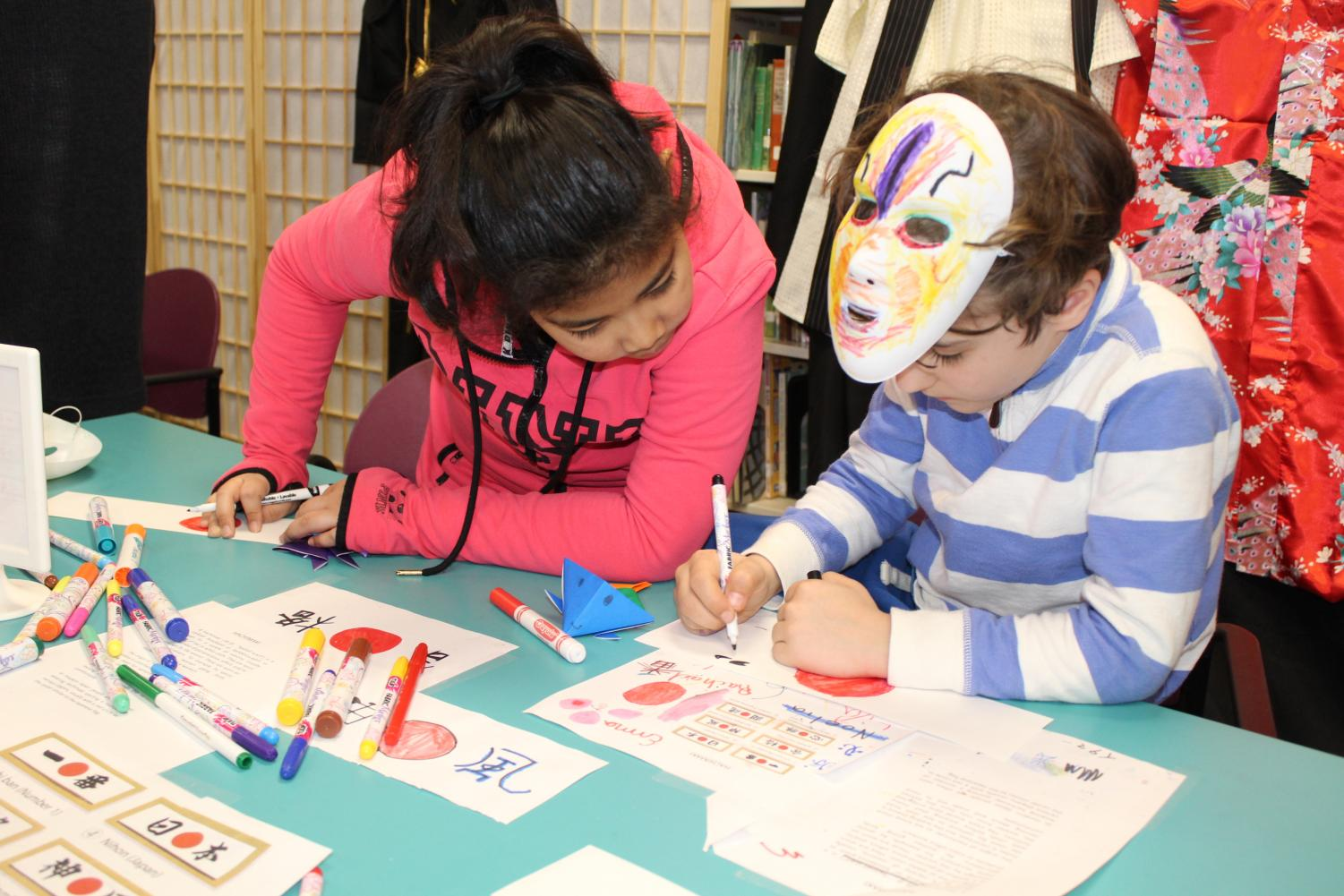 Manorhaven Elementary School students practice writing Japanese characters at a workshop