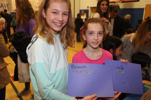 Two Daly Elementary School students show their finished projects in which they wrote their names in braille. This year's Family Literacy Night was an opportunity for young students to learn more about writing.