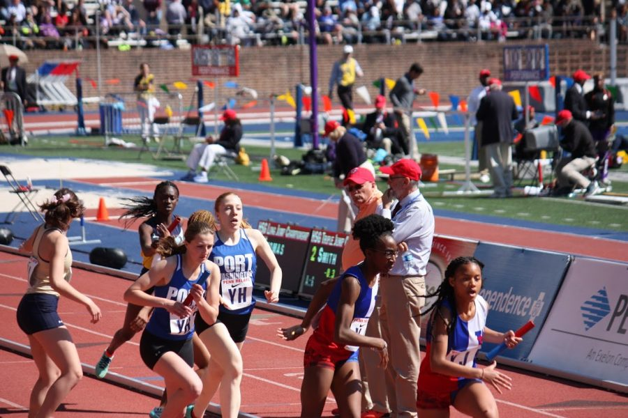 Senior captain Megan Mazzini passes the baton to senior captain Lucy Hurt during the 4x400 meter relays at the 2018 Penn Relays.