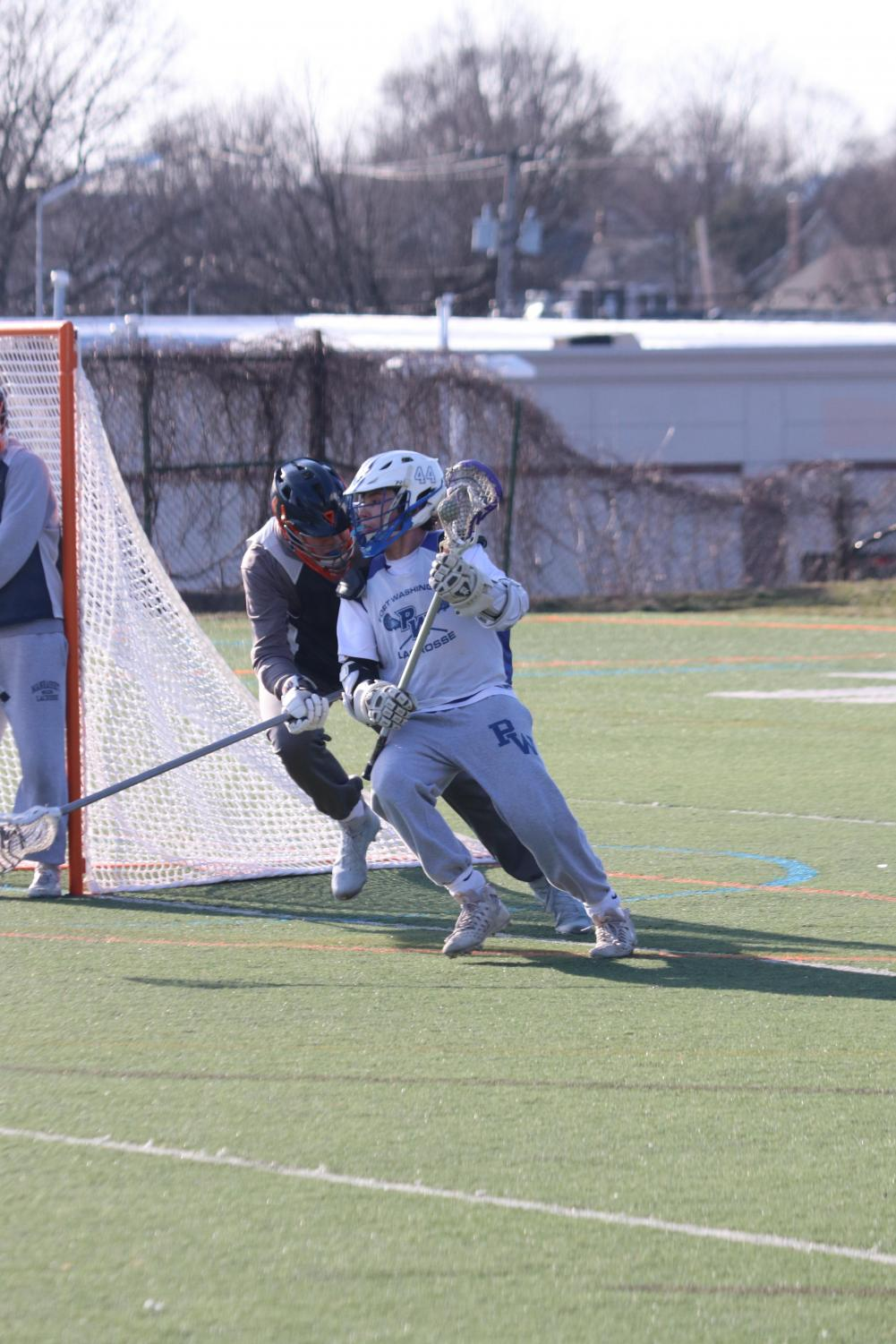 Senior John Athanasian looks to beat a defender around the net during a home game on April 12 against Kellenberg.  The Vikings went on to lose the match by a score of 12-16.