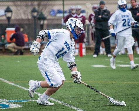 Senior Tommy Dover scoops the ball at a home game against North Shore on April 4. The Vikings won the game 13-12
