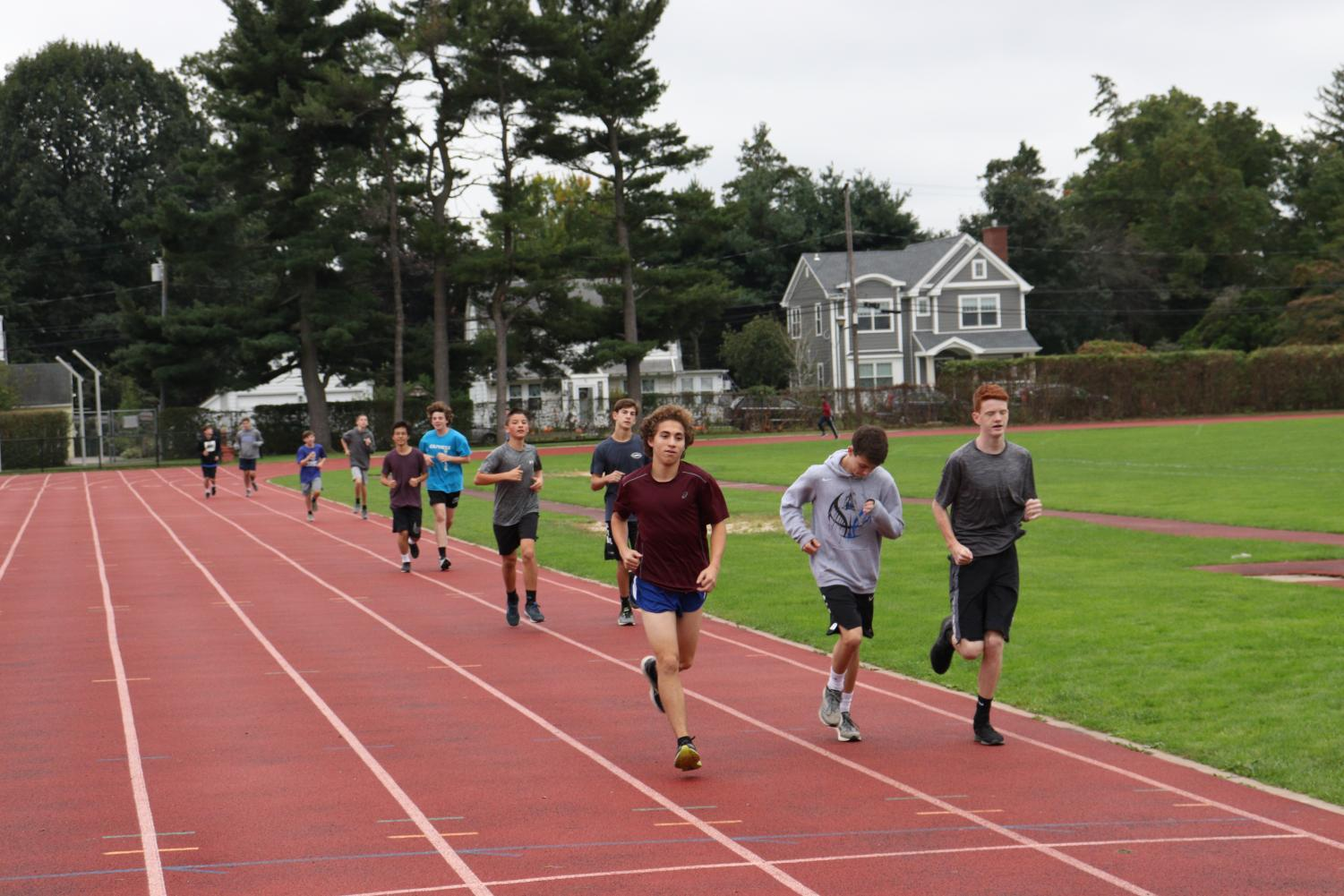 Max Friedman, Kevin Taylor, and Colin Funk finish the notorious Course-Mile-Course-Mile workout before their last league meet of the season.