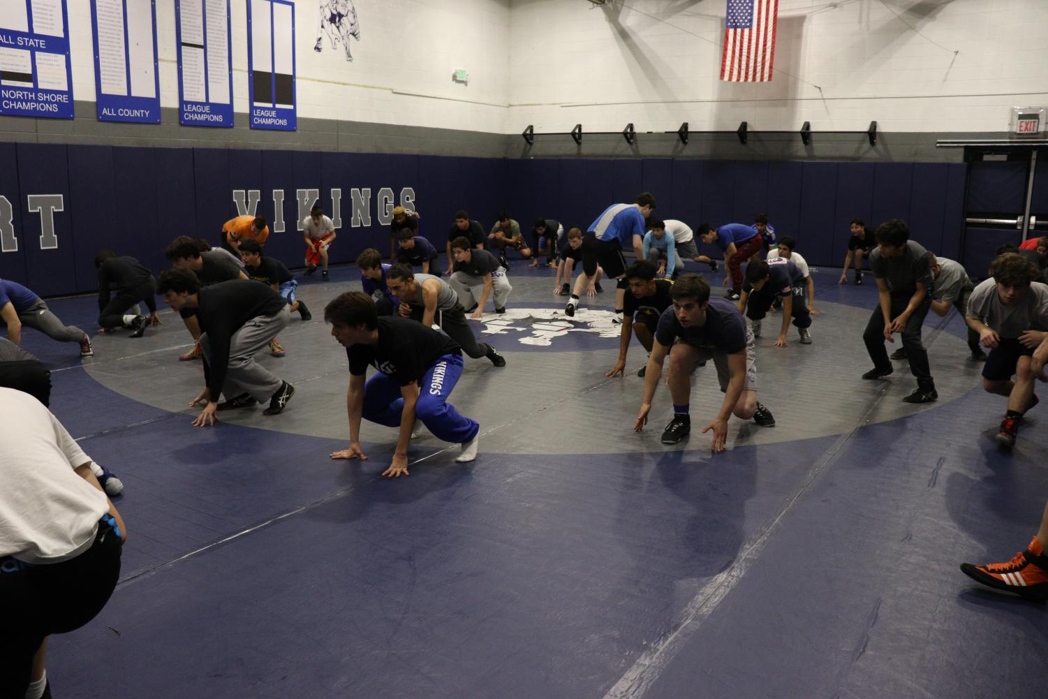 The varsity wrestling team prepares for its season during a workout in the wrestling gym.