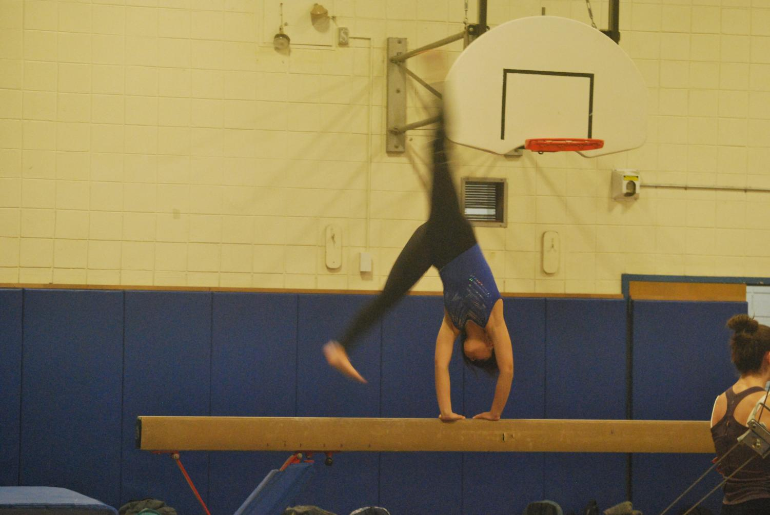 Freshman Kayla Quan practices on the balance beam, preparing for Port's first meet against Great Neck South.
