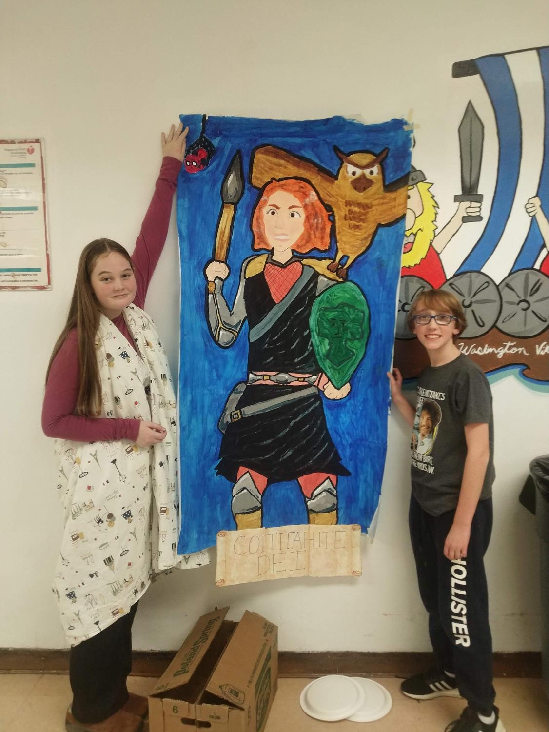 Sophomore Eloise Griffin and freshman Sam Nachimsan showcase their Saturnalia artwork at school event.