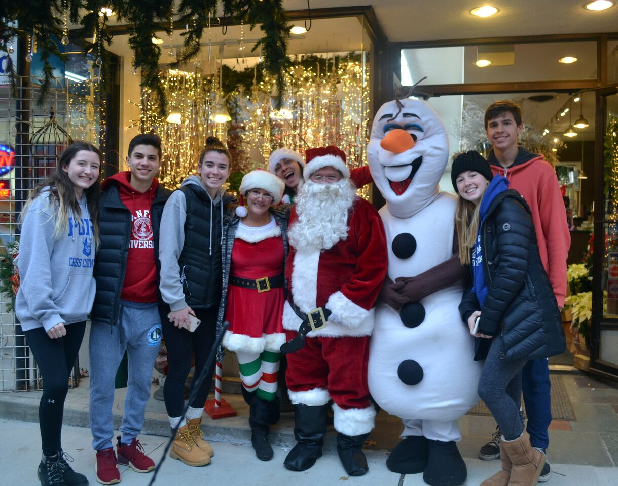 Students from Schreiber's Key Club stand alongside holiday characters as they help support local businesses at Port Holiday Magic.