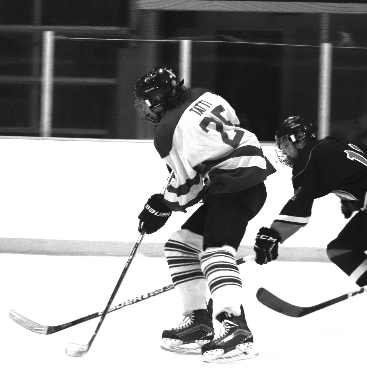Junior Finn Tatti advances the puck in a game against Manhasset on Jan. 15. The Vikings won that game with a score 3-2.