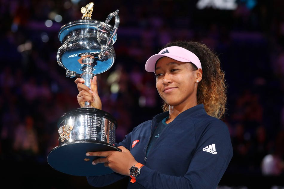 Naomi Osaka receives her trophy after winning the women's singles final, defeating Petra Kvitova in three sets.