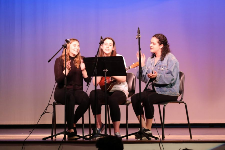 Last year's seniors, Valentina Scotto, Julia Gurlitz, and Emma Goldman perform an original song on stage at Shakespeare Day. This year's coordinators will be participating in similar performances.