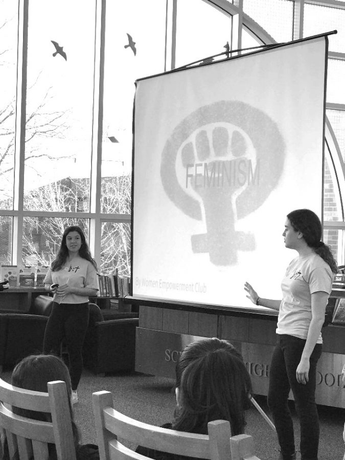 Seniors+Annie+Bandler+and+Hannah+Hirsch+conduct+a+presentation+meant+to+spread+awareness+to+students+in+Schreiber%27s+library.